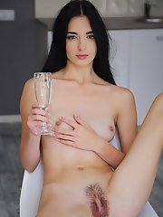 """After a glass of sparkling champagne, Benita takes off her t-shirt and spreads her legs wide open to flaunt her exquisite, unshaven pussy."""
